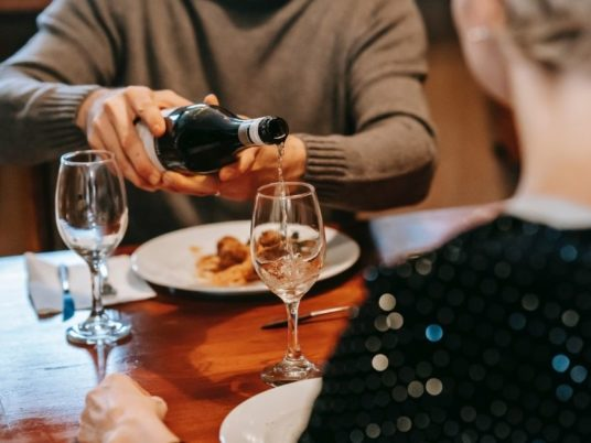 wine being poured over a meal